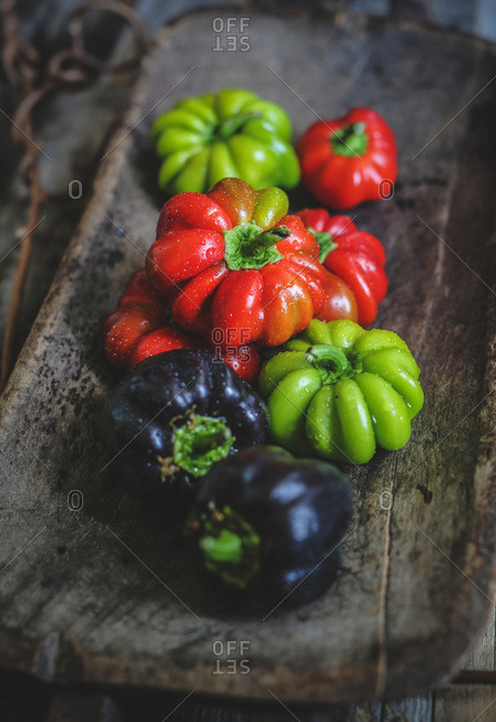 Colorful bell peppers in a wooden tray