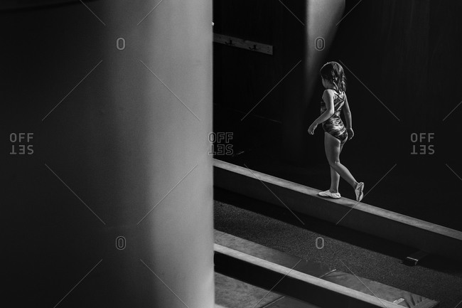 Young gymnast walking on a balance beam