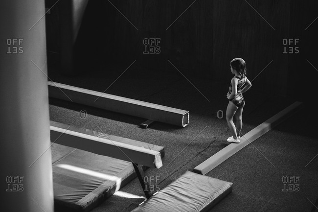 Young gymnast standing on a balance beam