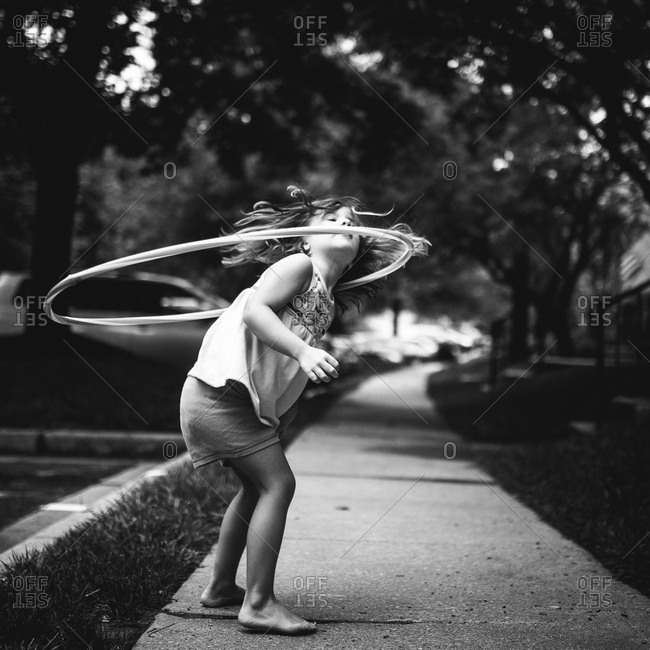 Girl twirling a hula hoop around her neck