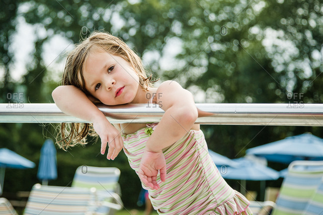 Girl resting her head on railing outdoors
