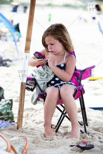 Girl playing with a mobile phone while sitting by herself in a beach chair