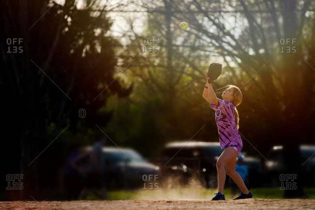 Girl about to catch a softball