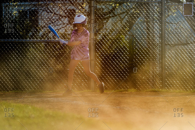 Girl swinging bat while playing softball