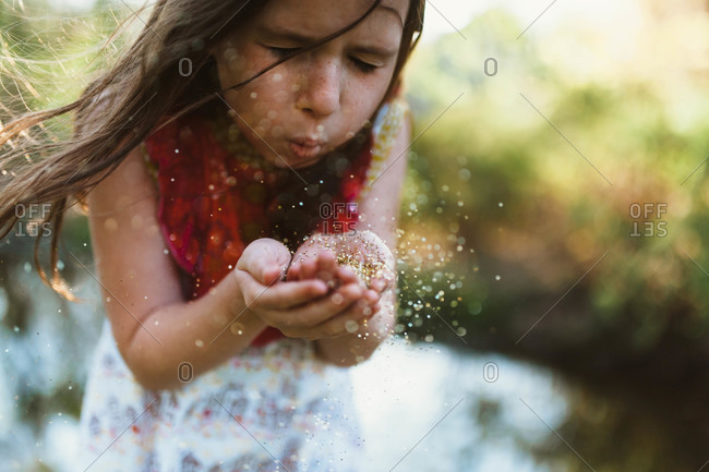 Girl blowing dirt from hands