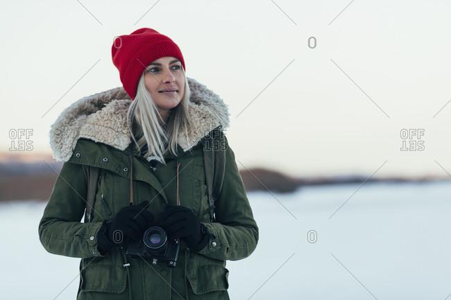 Thoughtful woman with camera enjoying winter season