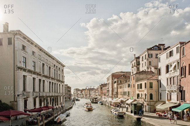 Canal amidst city buildings against sky, Venice, Veneto, Italy