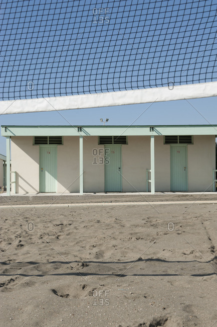 Volleyball net and huts at beach on sunny day