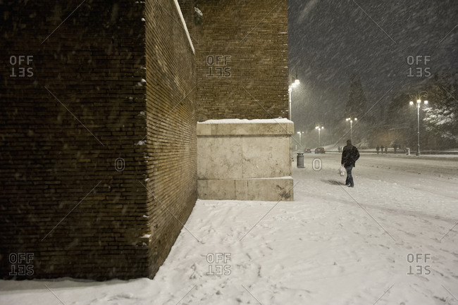 City building and pedestrian in snow storm at night
