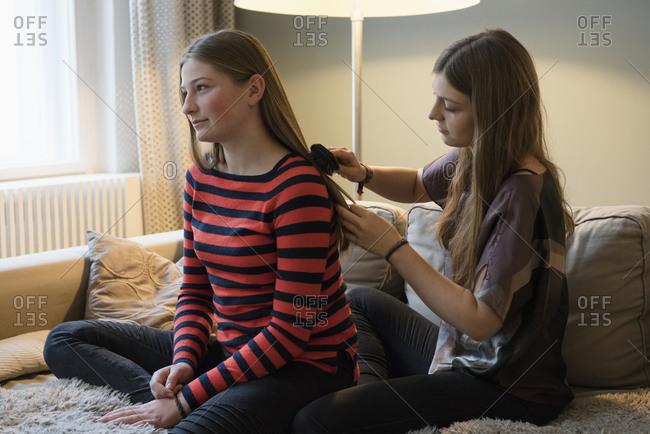 Young woman brushing sister's hair at home