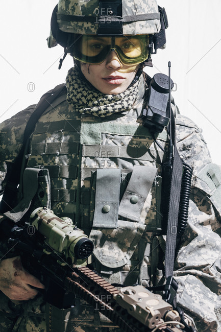 Portrait of female soldier carrying rifle and standing against white background