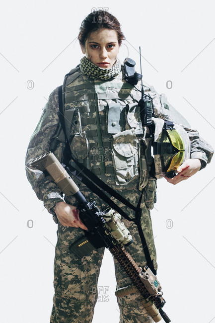 Portrait of soldier holding rifle and helmet standing against white background