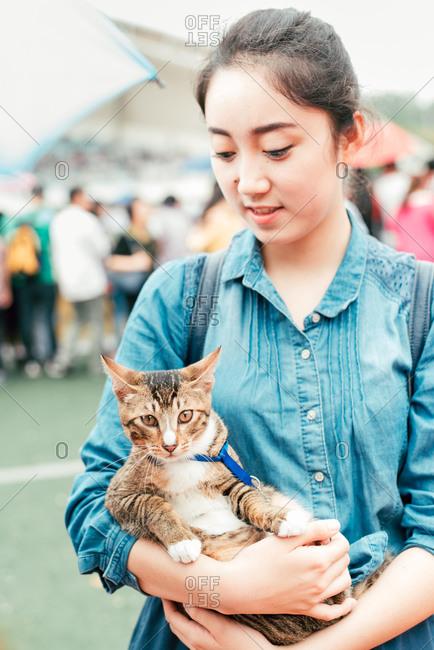 April 16, 2016: Young woman holding a cat, Guangzhou, China
