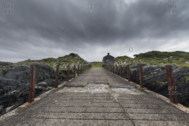 Broken, worn and weathered concrete path under storm clouds; Argyll and Bute, Scotland