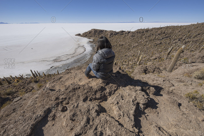 Woman sitting on an island of rock and cactus called Incahuasi; Uyuni, Bolivia
