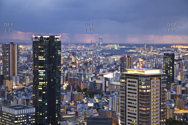 Storm clouds over a city illuminated with lights; Osaka, Japan
