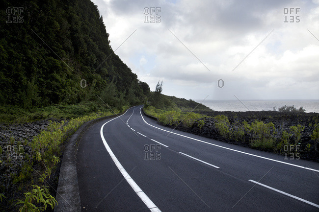Seafront road under a dramatic sky; Reunion Island, France