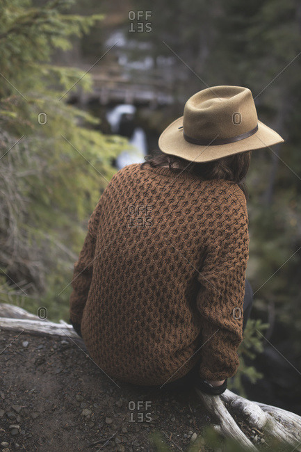 Woman in hat perched on ledge overlooking river in Girdwood, Southcentral Alaska.