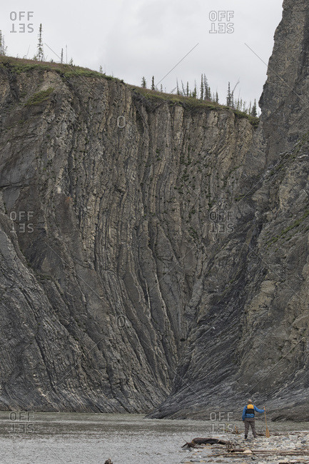 Man standing at the mouth of the Peel Canyon along the Peel River, part of the Peel Watershed; Yukon, Canada