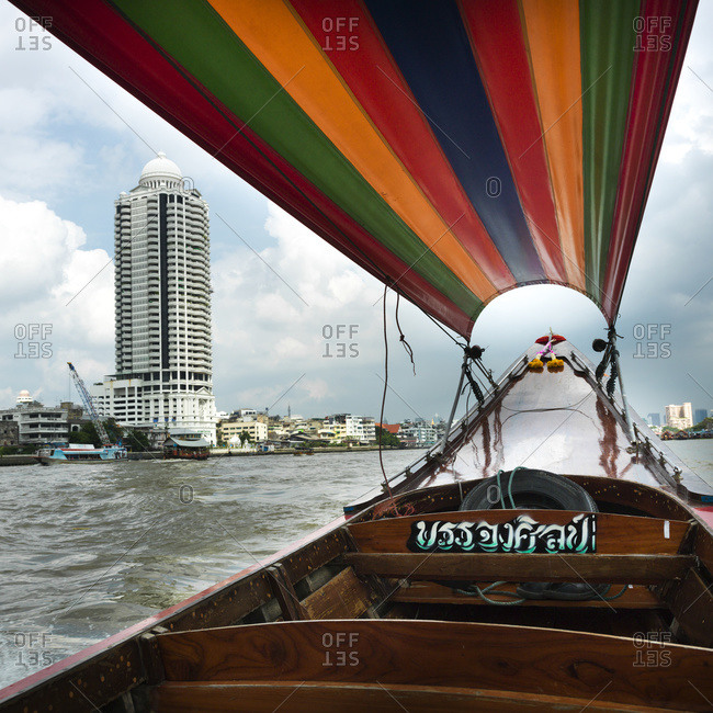 Boat with colourful covering and buildings along the shoreline; Bangkok, Thailand