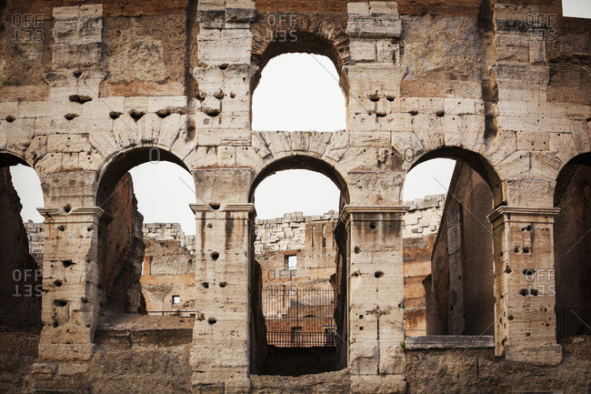 Old stone wall of Colosseum with arches; Rome, Italy