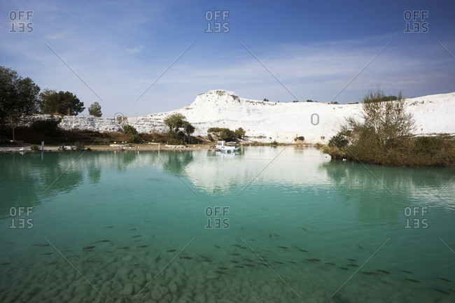 Turquoise water in a pool reflecting a white wall of mineral deposits; Pamukkale, Turkey