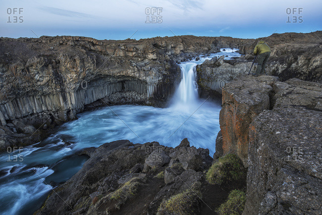 The basalt column and waterfall known as Aldeyjarfoss in Northern Iceland, a person stands at the top and photographs them; Iceland