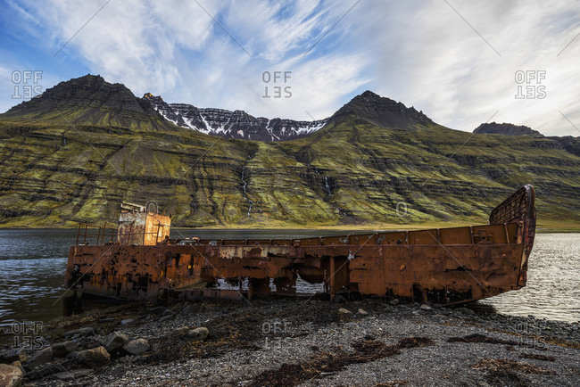 Old shipwreck along the water in Mjoifjordur, East Iceland; Iceland