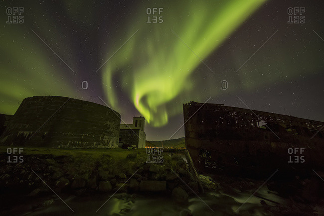 Northern lights over top of the town known as Djupavik along the Strandir Coast, here they are dancing above the old herring factory and shipwreck; Djupavik, Iceland