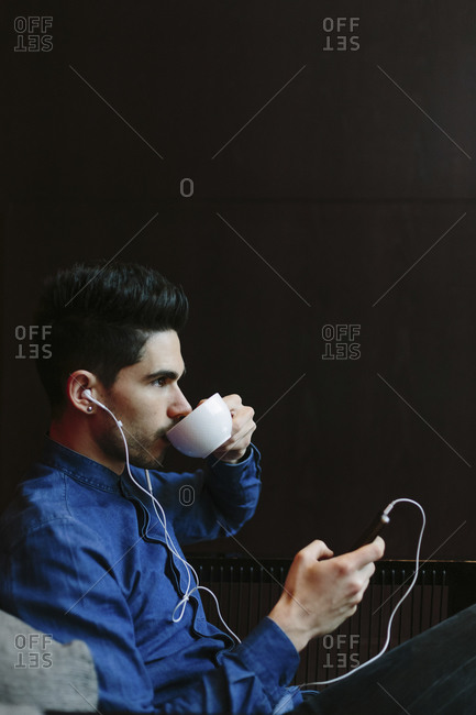 Profile of young man listening to music with earphones and drinking coffee