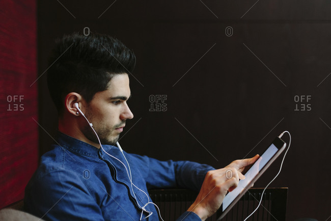 Profile of young businessman with earphones using digital tablet in front of black background