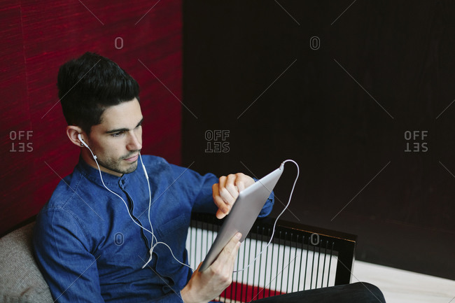 Young businessman with earphones using digital tablet
