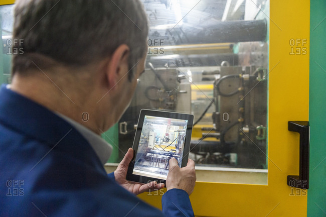 Manager doing quality assessment in plastics factory with a tablet
