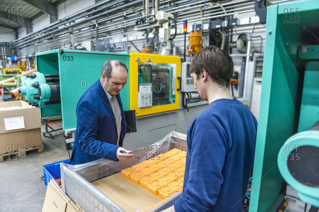 Manager and worker looking at plastic products in factory