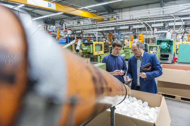 Manager and worker looking at plastic products in factory together