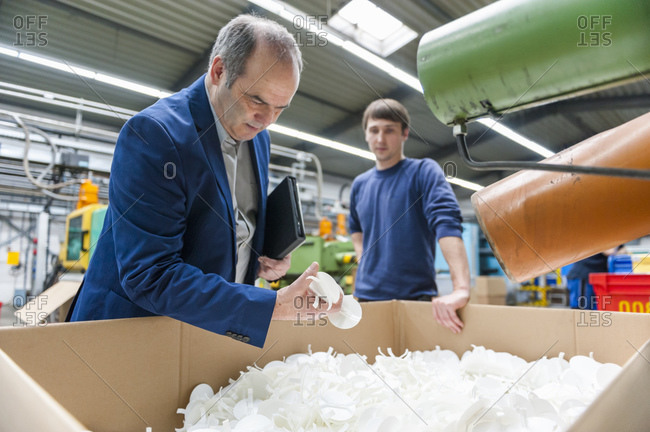 Manager and worker looking at  products in plastics factory together