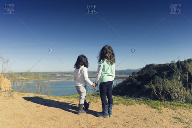 Back view of two little girls looking at a lake