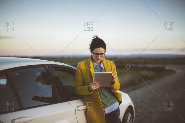 Woman using digital tablet at car