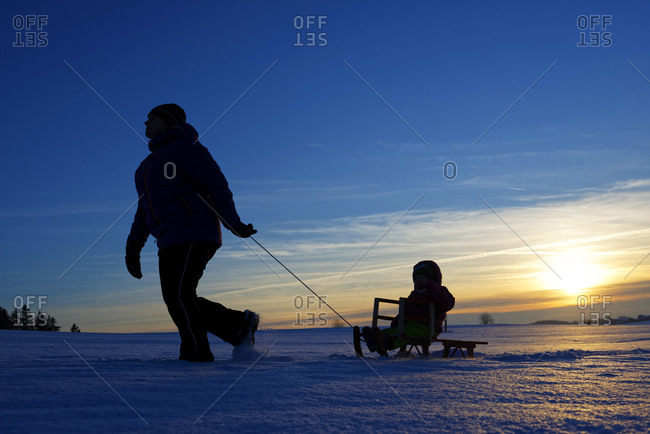 Mother and daughter sledding at sunset