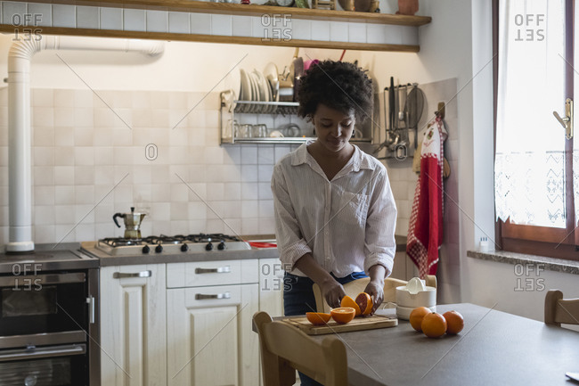 Young woman cutting oranges for squeezing juice
