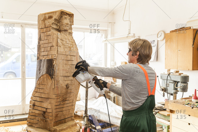 Wood carver working on sculpture with chainsaw