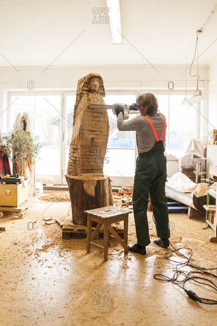 Wood carver working on chainsaw sculpture