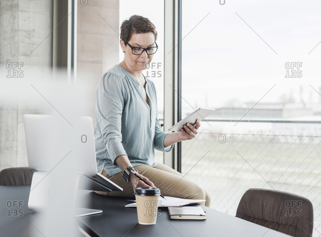 Businesswoman with digital tablet and notepad in office