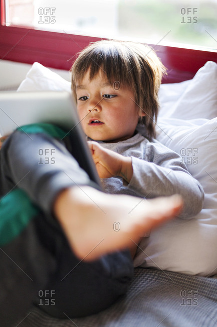 Little boy on a couch using digital tablet