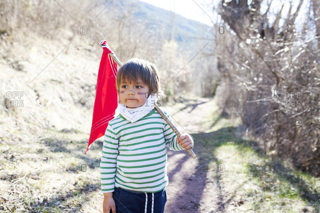 Portrait of little boy with red flag playing hero