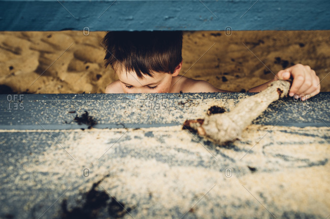 Little boy hiding under steps on a beach