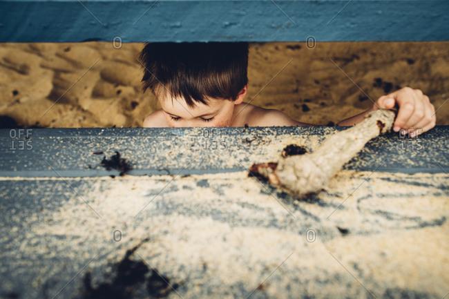 Little boy hiding under steps on a beach