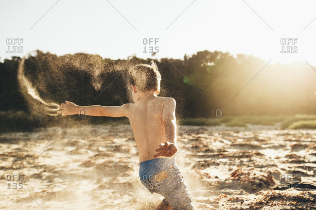 Boy running on the beach throwing sand