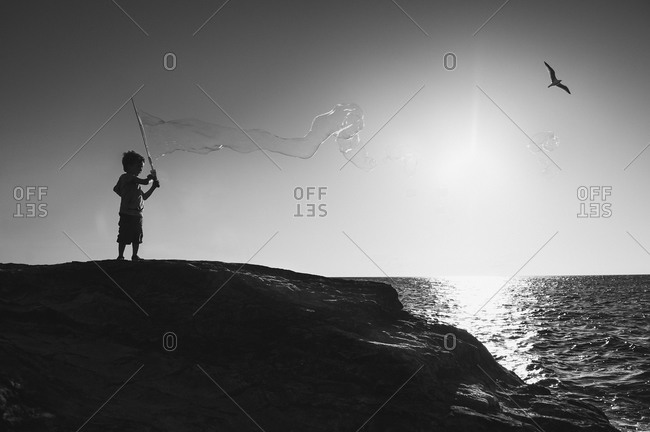 Silhouette of boy making a large bubble