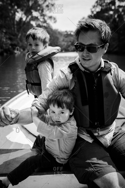 Father and two boys on a row boat